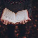 djevojka u puloveru čita knjigu crvenih korica.