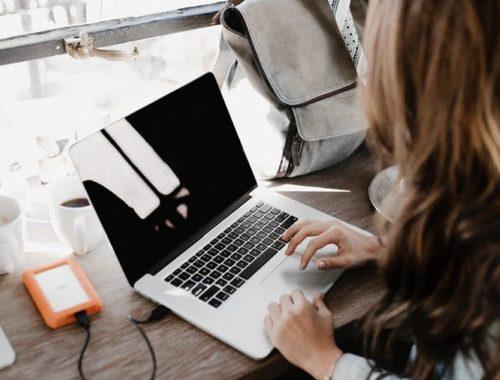 Žena smeđe kose, na laptopu, pored prozora