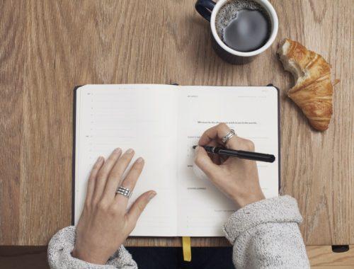 žena s rokovnikom, pije kavu i jede pecivo