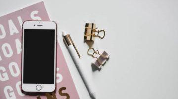 Mobitel na ružičastoj bilježnici s bijelim slovima i kemijska olovka