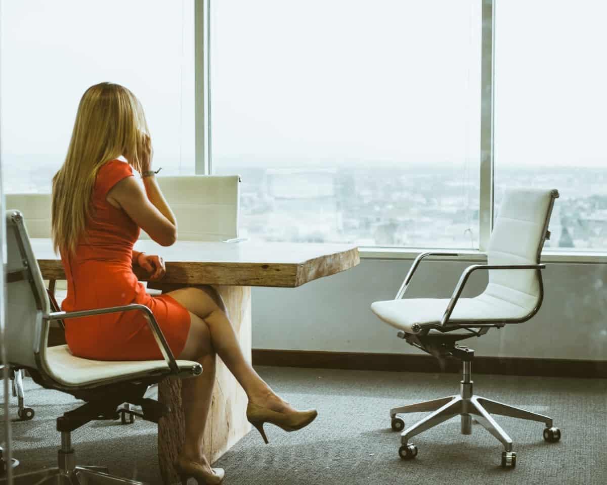 Žena u narančastoj haljini sjedi u uredu s pogledom na grad