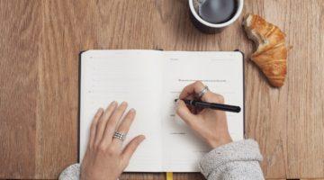 Pisanje u bilježnicu, kroasan i kava