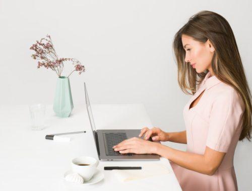 Žena u ružičastoj haljini sjedi pored laptopa