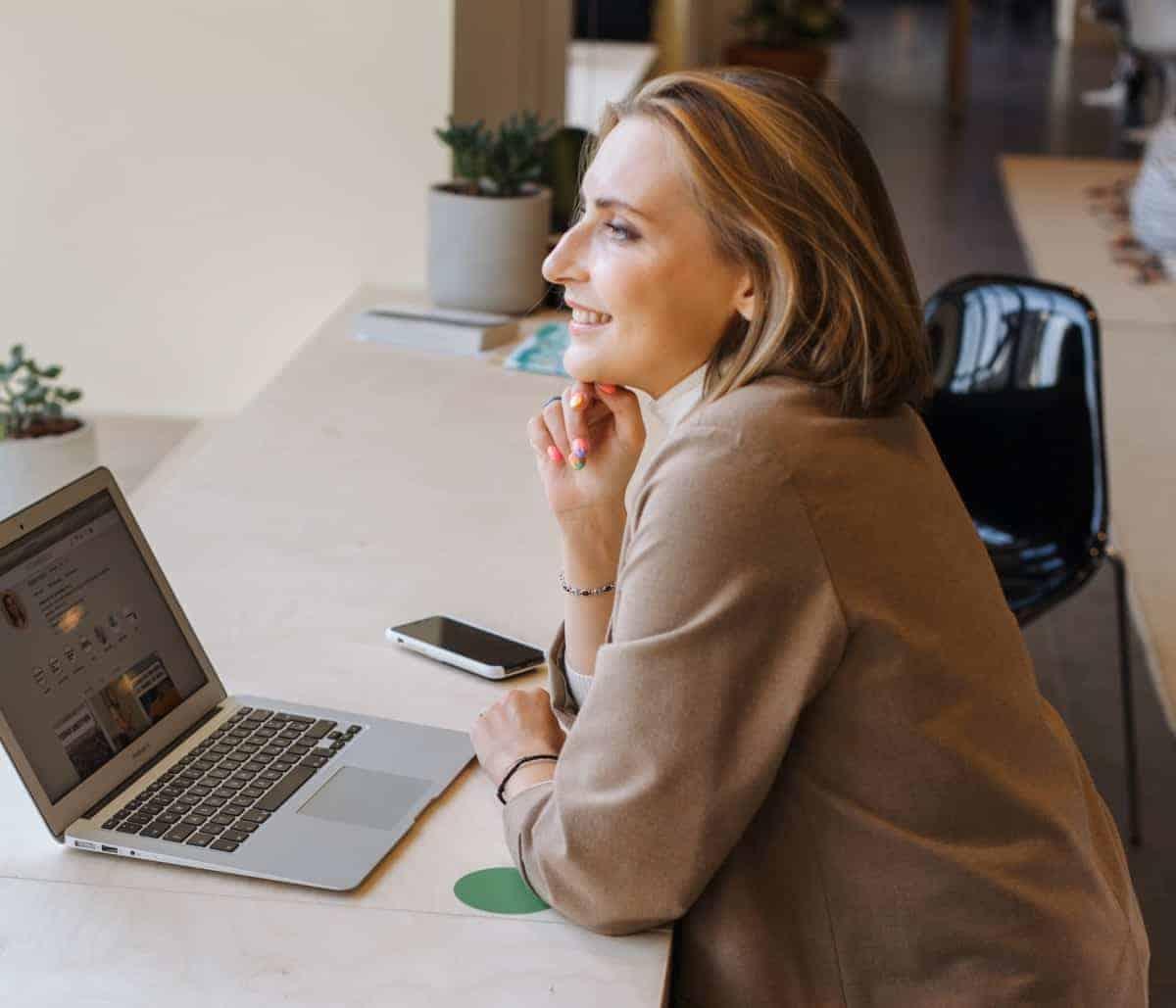 Žena sa smeđim sakoom i laptopom