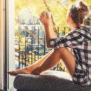 Žena pije kavu i gleda kroz prozor