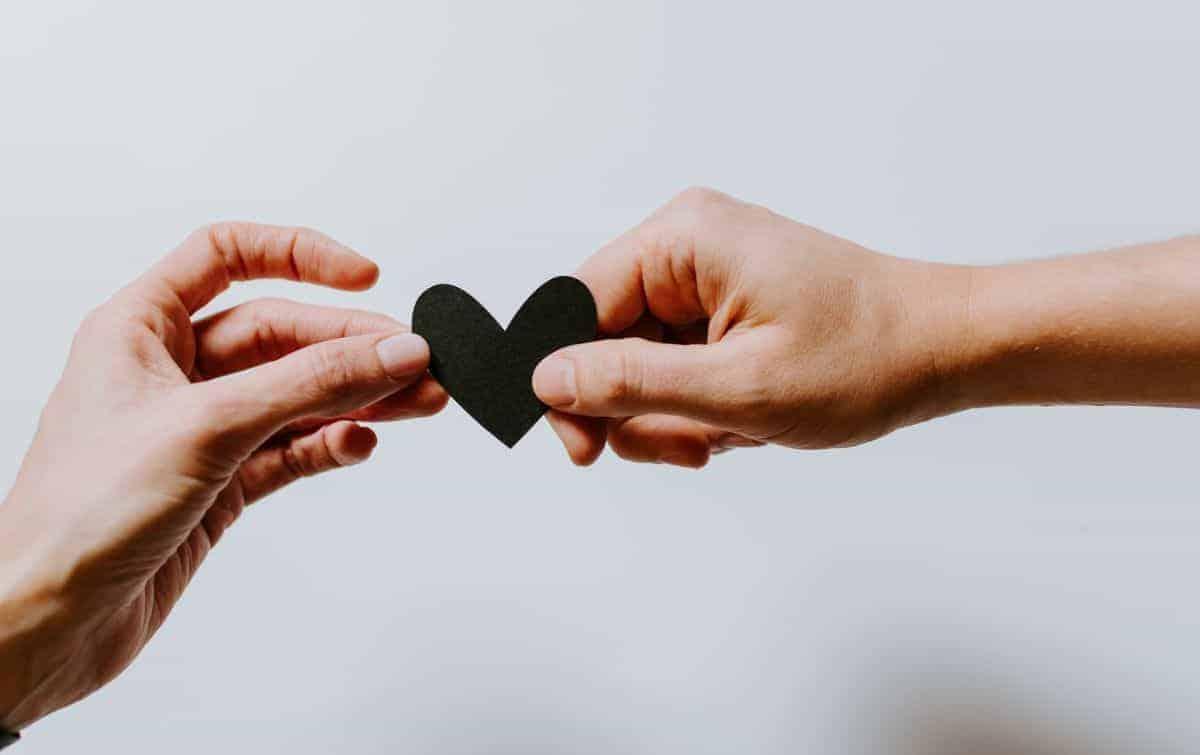Dvije ruke s crnim srcem u sredini koje pružaju pomoć i podršku
