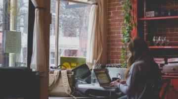 Žena sjedi za stolom u kafiću i radi na laptopu